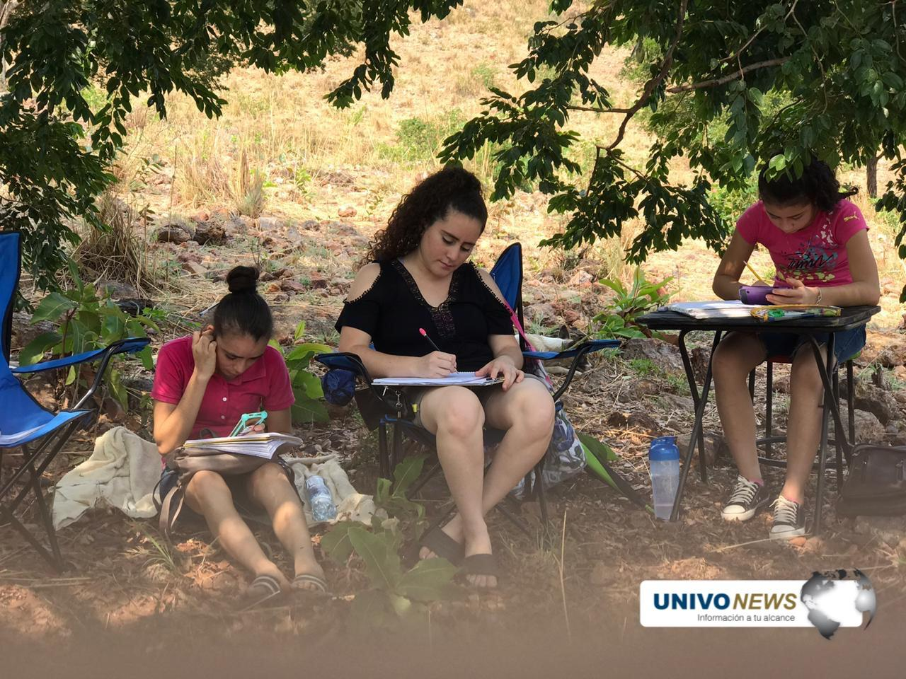 Photo of Cuatro jóvenes buscan señal de internet en una zacatera para recibir sus clases virtuales